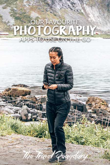 A girl dressed in black checks her phone after taking a photo in Lofoten, Norway