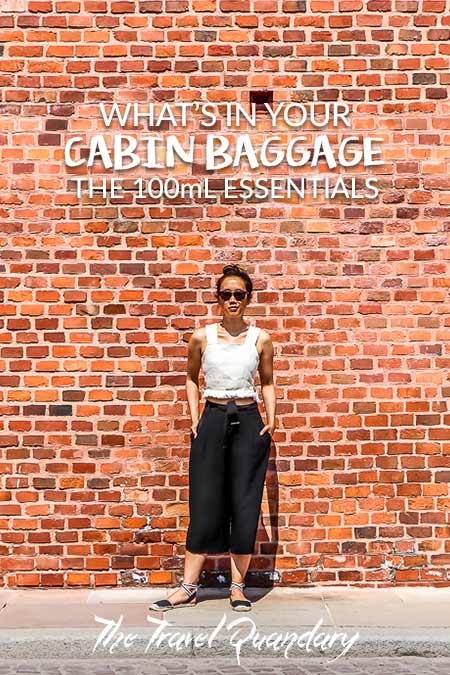 Jasmine of The Travel Quandary poses in front of a red brick wall in Krakow, Poland   Cabin Baggage Liquids Allowance