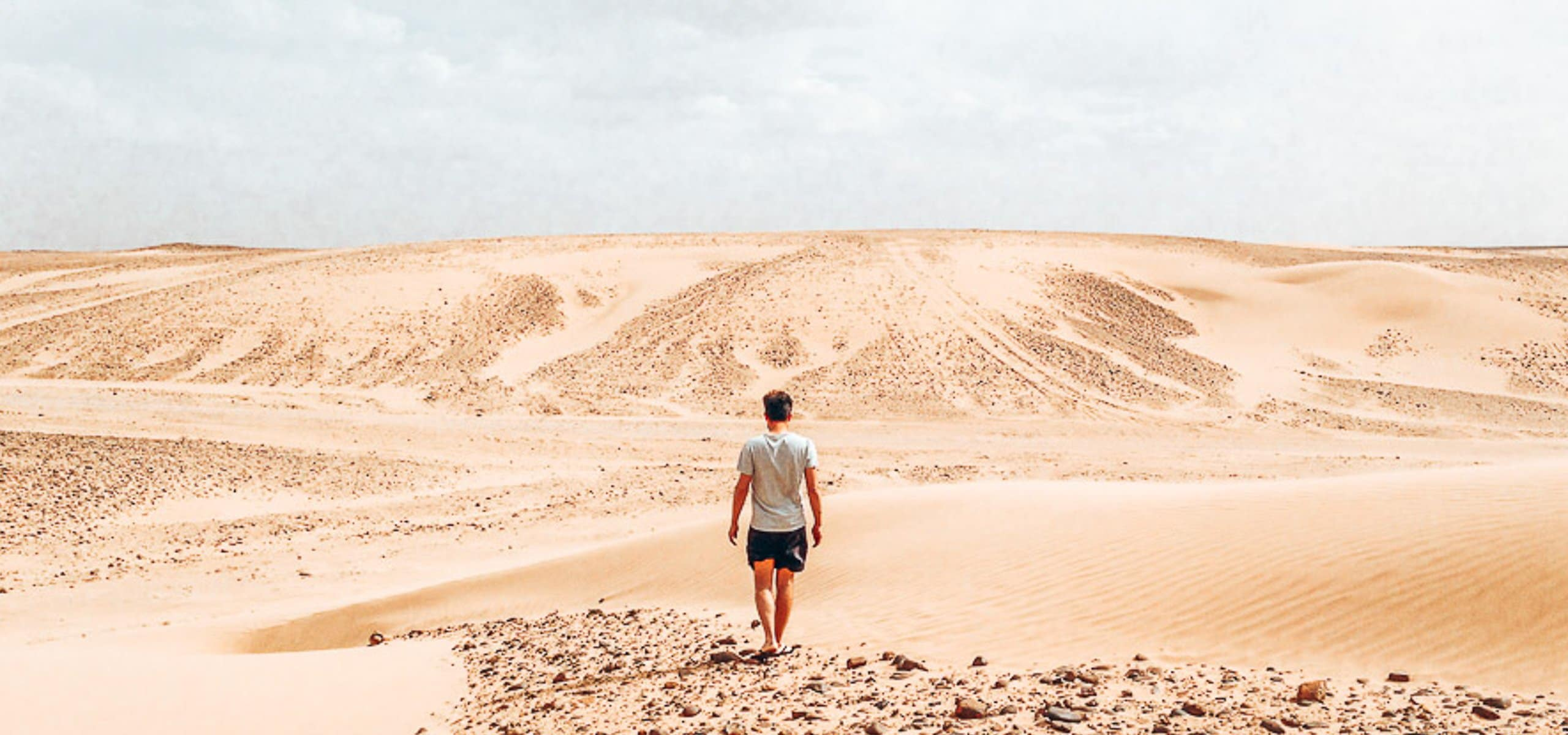 A man walks in the middle of the Sahara Desert, Morocco