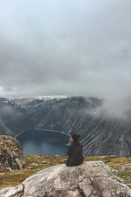 Jasmine sitting on a rock taking in the fjord views - Trolltunga, Norway
