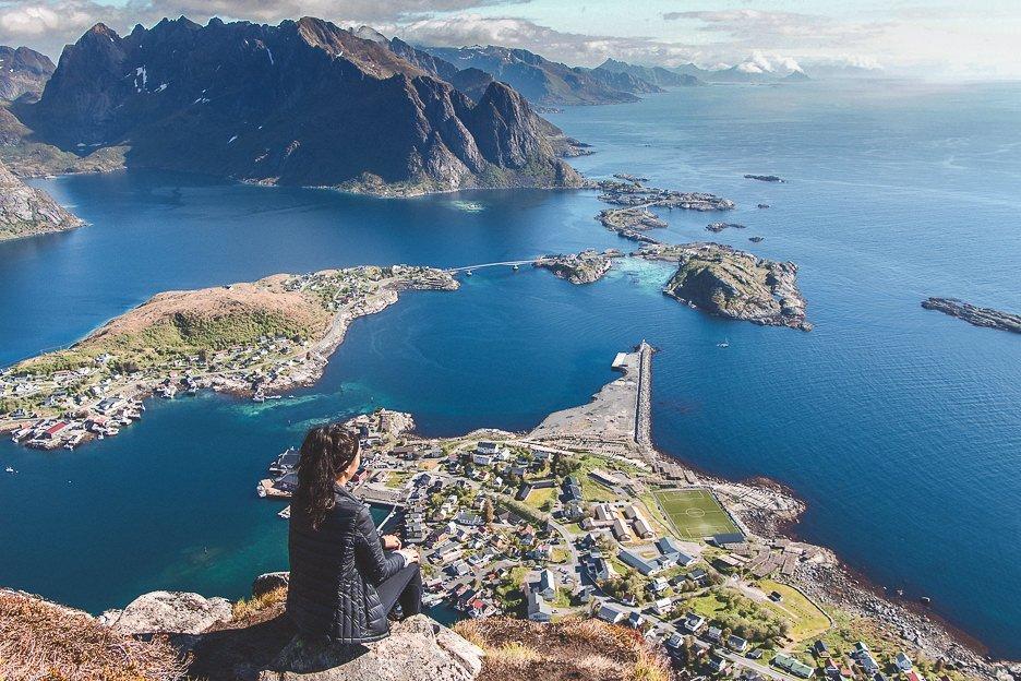 Jasmine sits at the top of Reinebringen looking out at Reine - Lofoten Islands, Norway