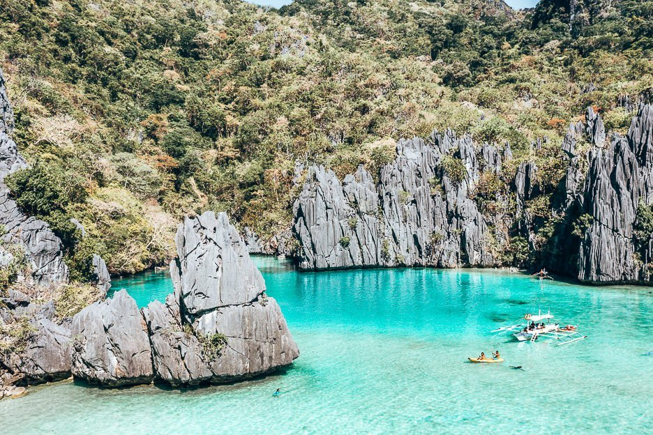 Kayakers enjoying Cadlao Lagoon surrounded by jagged rocks, El Nido