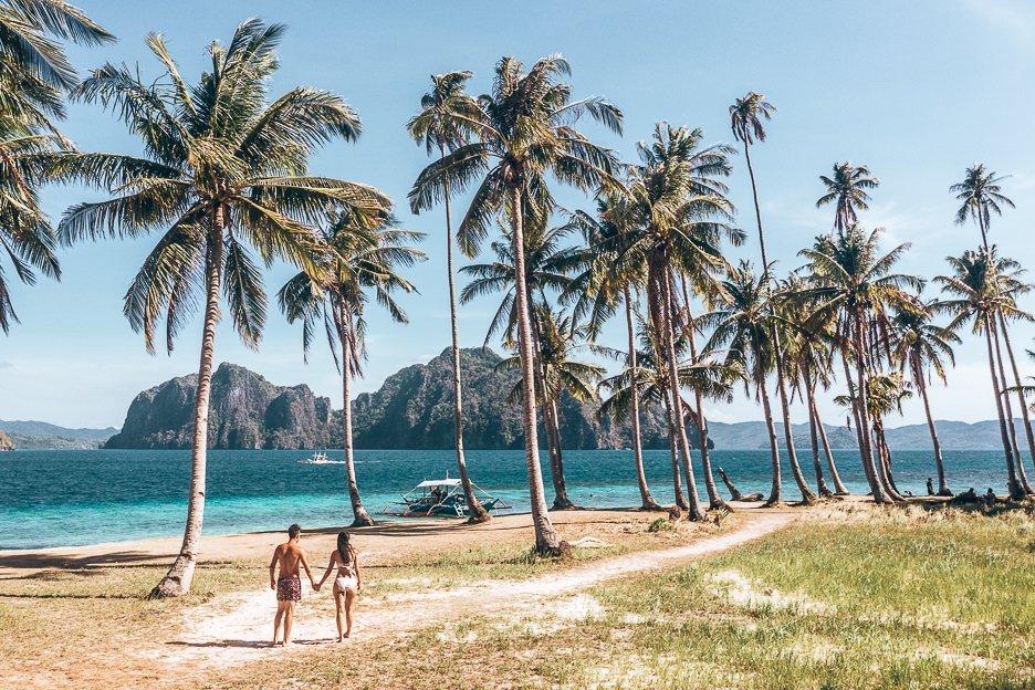 A couple walk hand in hand underneath palm trees on Pinagbuyutan Island, El Nido