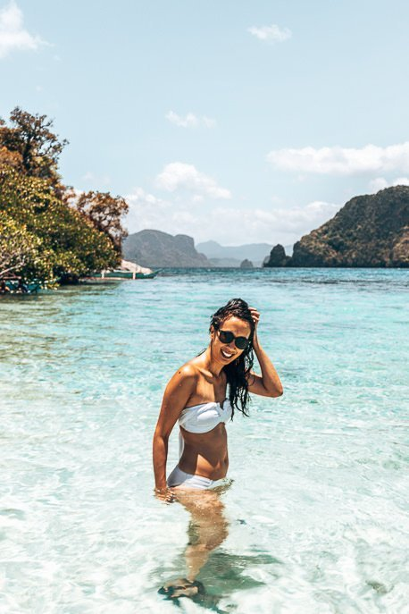 A girl in a white bikini and sunglasses smiles while posing in the water off Snake Island, El Nido