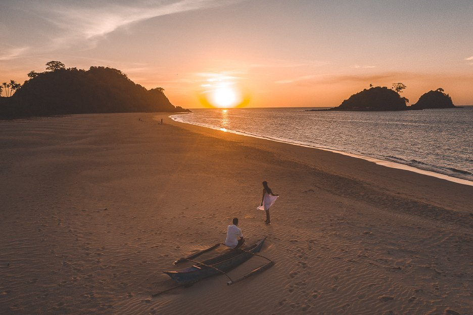 A couple next to a beached boat watching the sunset on Nacpan Beach, El Nido