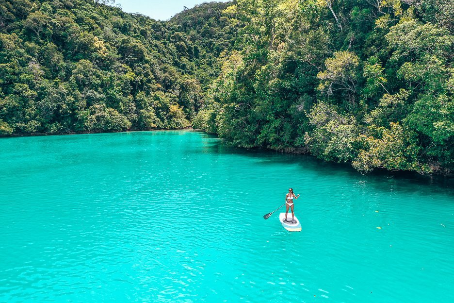 A lone woman stand up paddle boarding in Sugba Lagoon, Siargao