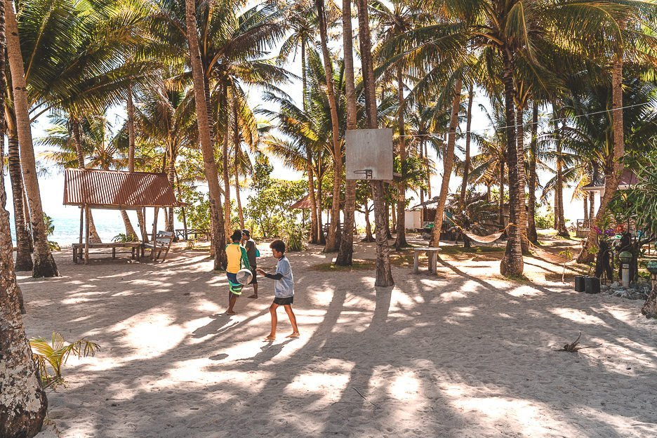 Three local boys playing basketball on a sandy court on Guyum Island, Siargao