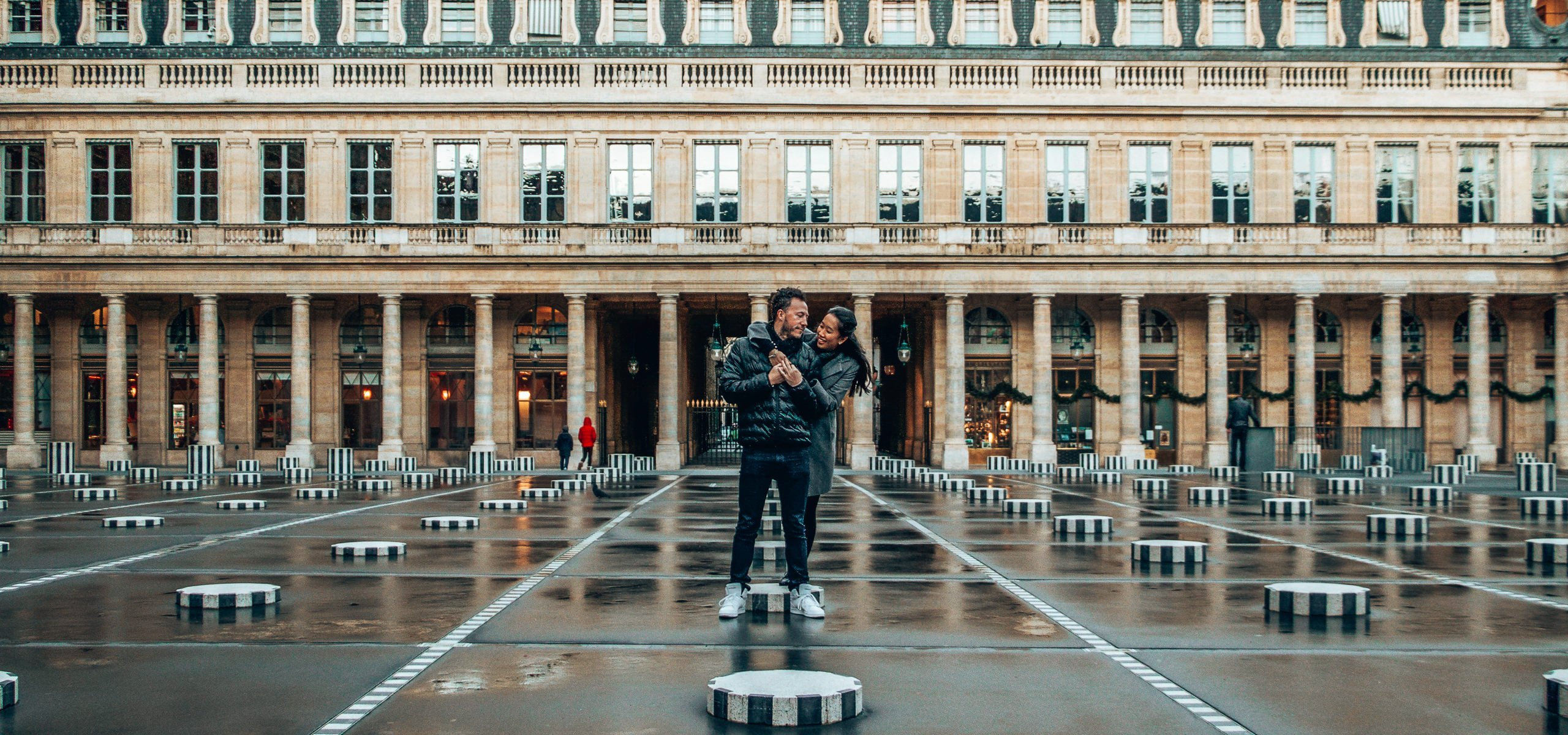 A woman wraps her arms around a man at Palais Royale, Paris - 5 Tips When Dating and Travelling