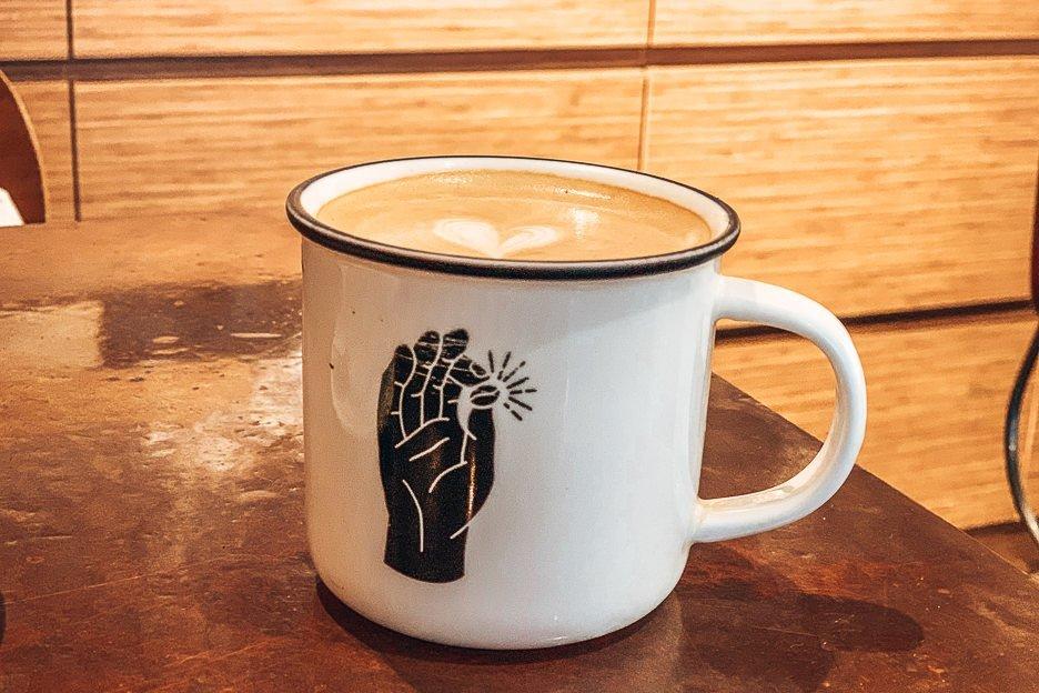 A large latte in a tin mug at Urban Coffee Roaster, Hong Kong
