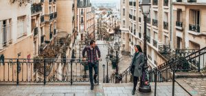 A couple stand on the top of stairs in Montmartre, Paris