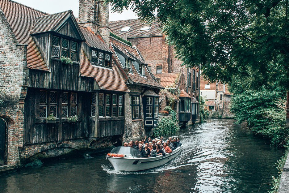 A boat goes by on the canal in front of Bonifacius Bridge in Bruges, Belgium