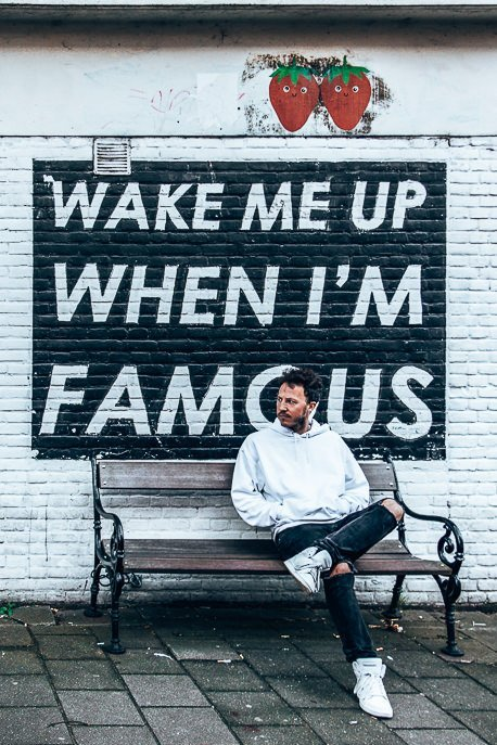 Sitting in front of the Wake Me Up When I'm Famous sign, Amsterdam