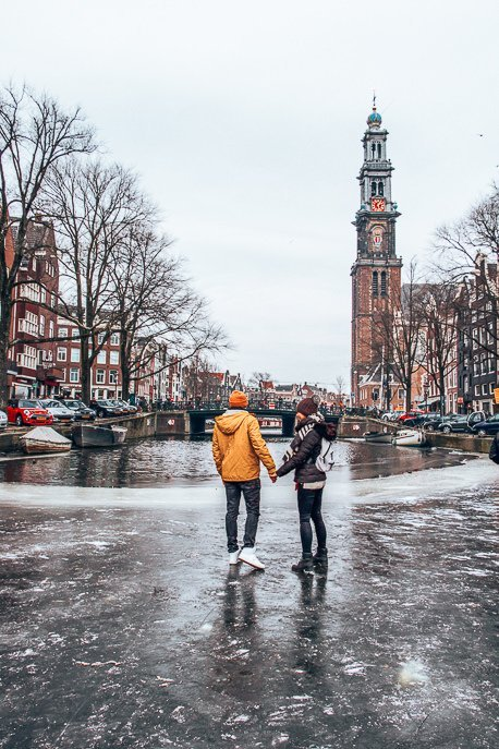 A couple stand on a frozen canal in front of Westerkerk, Amsterdam