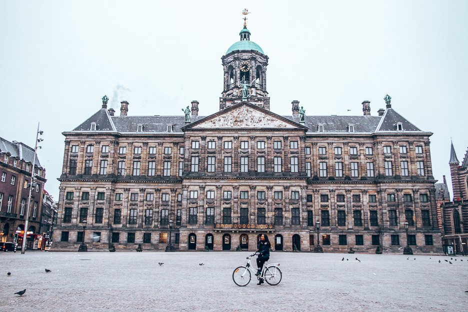 Posing in front of the Royal Palace on a bicycle in Dam Square, Amsterdam