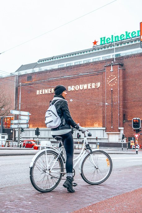 Riding a bicycle in front of the Heineken Brouwer'j, Amsterdam