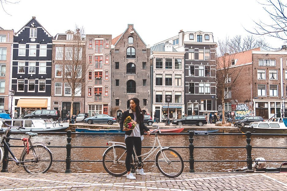 Holding a bicycle and bunch of tulips next to the canals in Amsterdam, The Netherlands