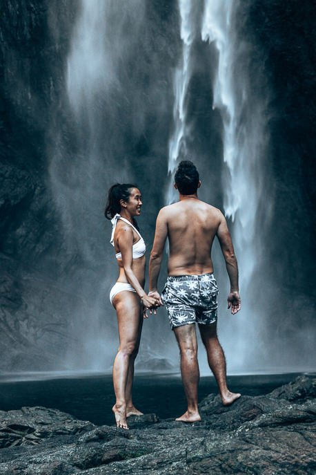A couple stand underneath Wallaman Falls. Australia's largest single drop waterfall in tropical north Queensland