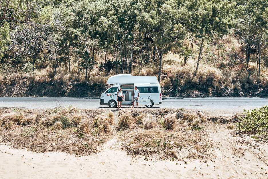 A couple stand in front of a Britz campervan on the Captain Cook Highway in Tropical north Queensland
