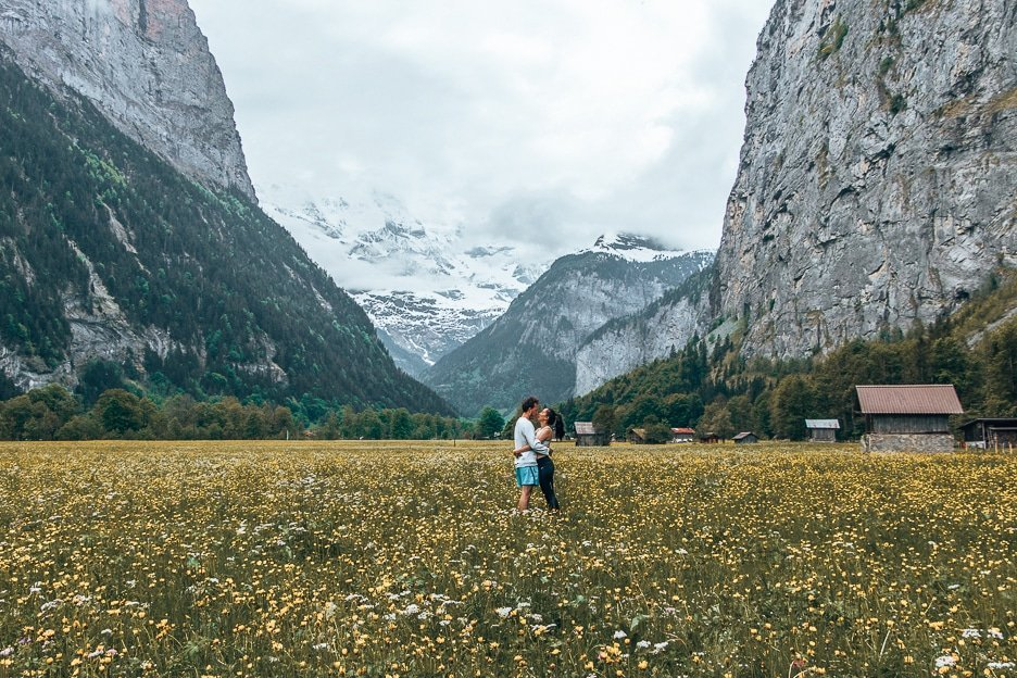 A couple kissing in a field of yellow wildflowers in Lauterbrunnen, Switzerland - About The Travel Quandary