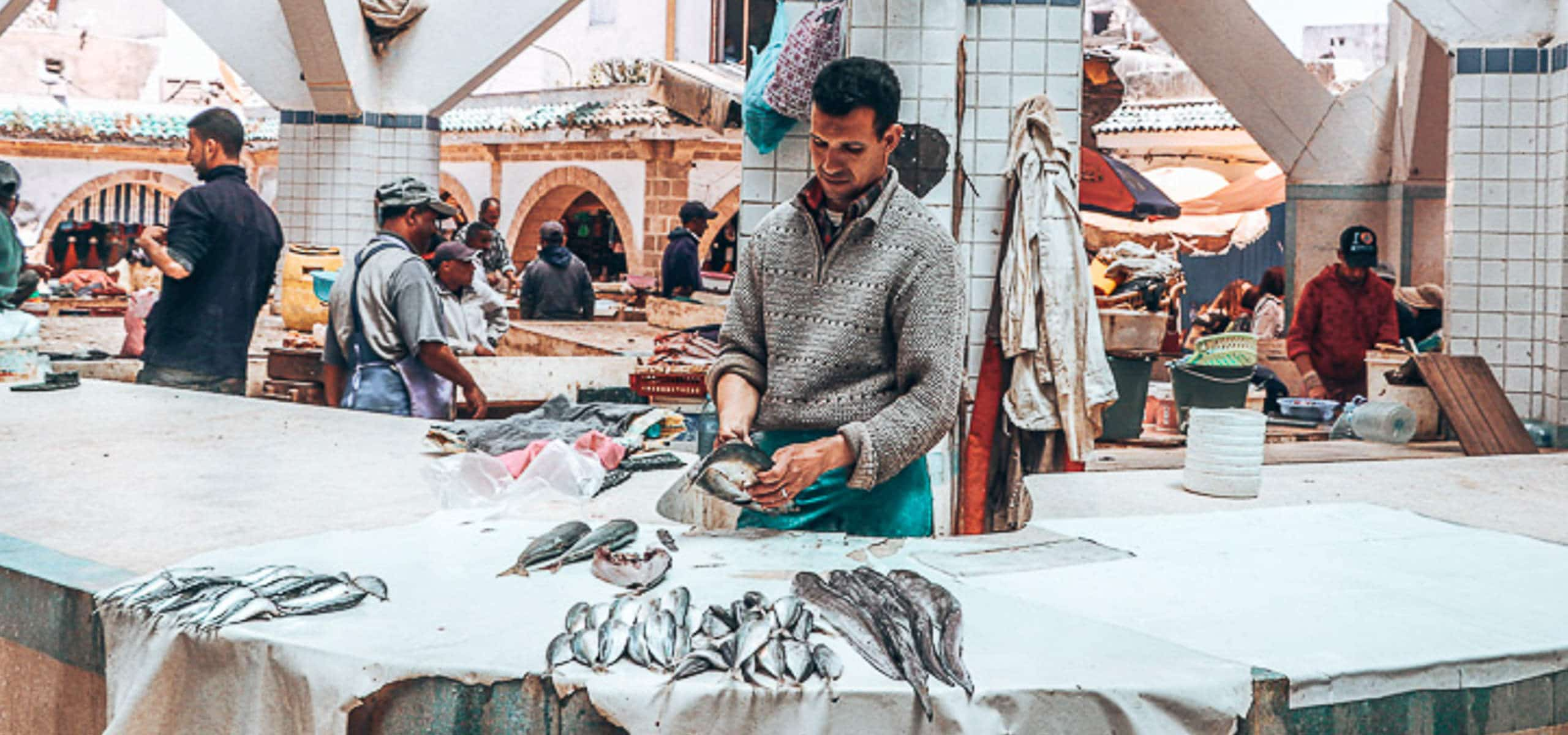 A man cleans fish at the Marche aux Poissons in Essaouira, Morocco