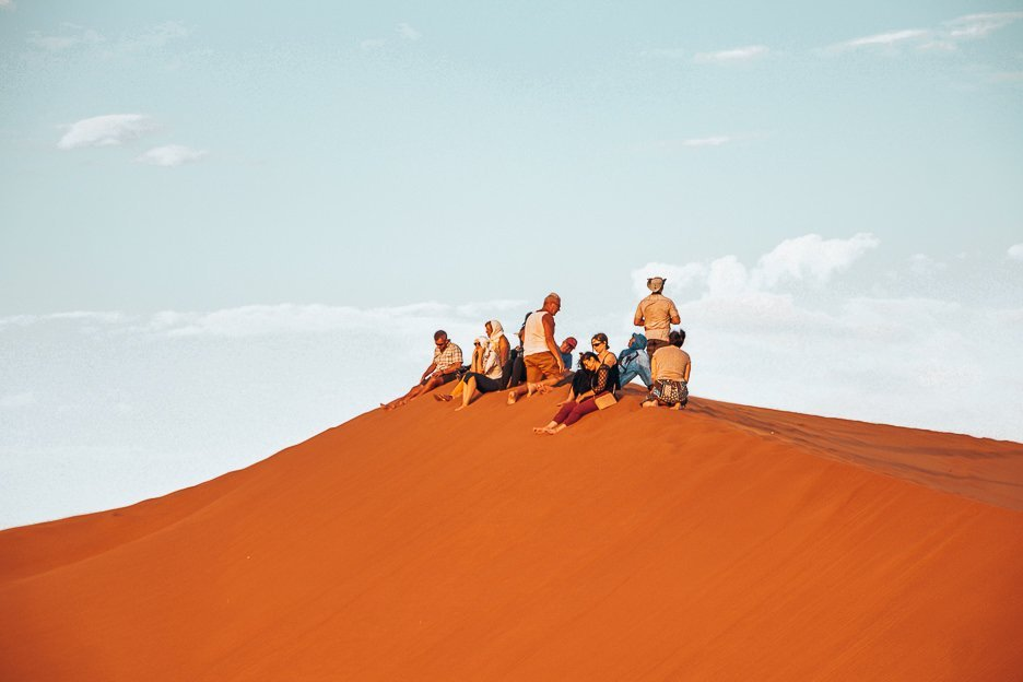 A group sit on the peak of a sand dune in the Sahara Desert, Morocco