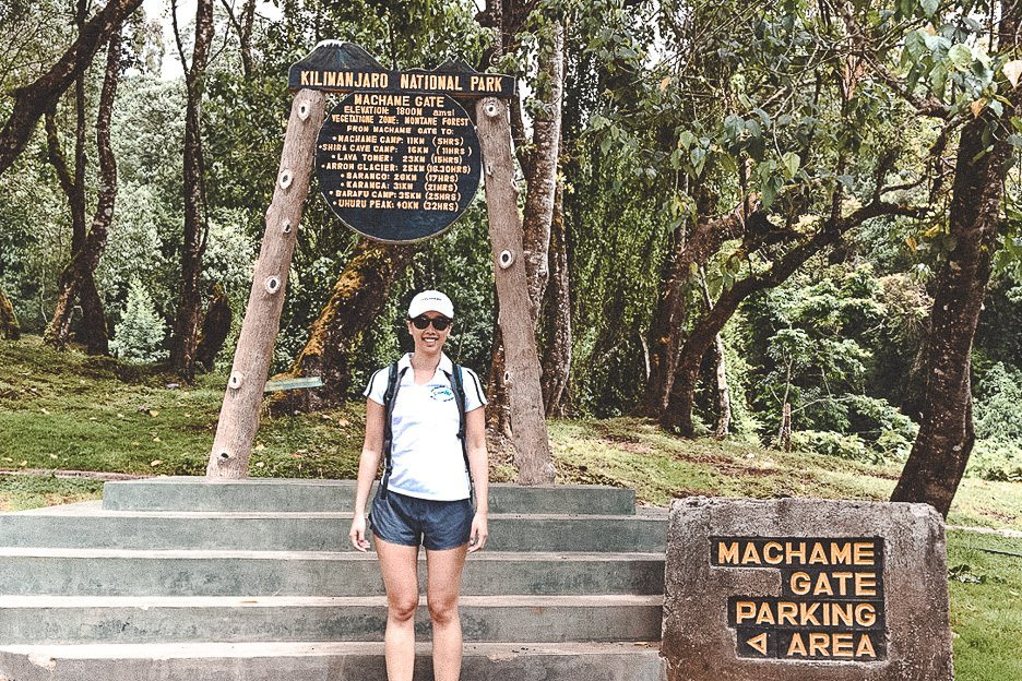 Jasmine stands at Machame Gate at the beginning of a 7 day hike of Mt Kilimanjaro