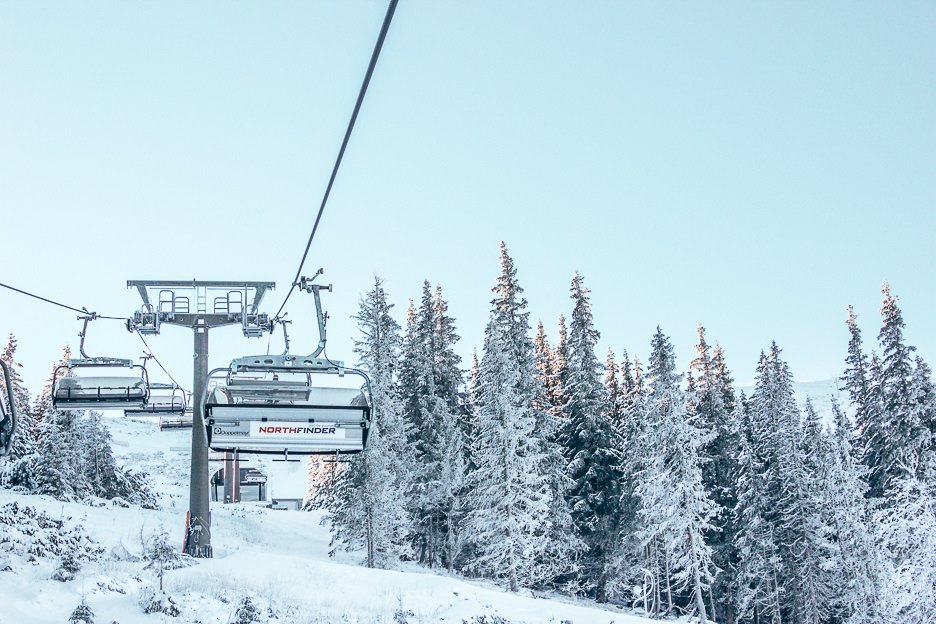 Riding the chairlift in Jasna Nizke Tatry past snow covered pine trees - Snowboarding in Slovakia