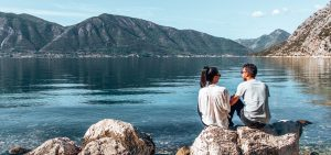 A couple sit on a rock next to the water in Montenegro