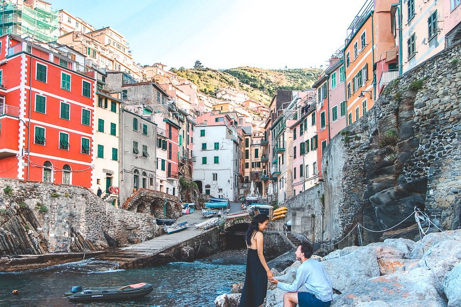 A couple sit on the rocks in the harbour of RIomagiorre, Cinque Terre, Italy