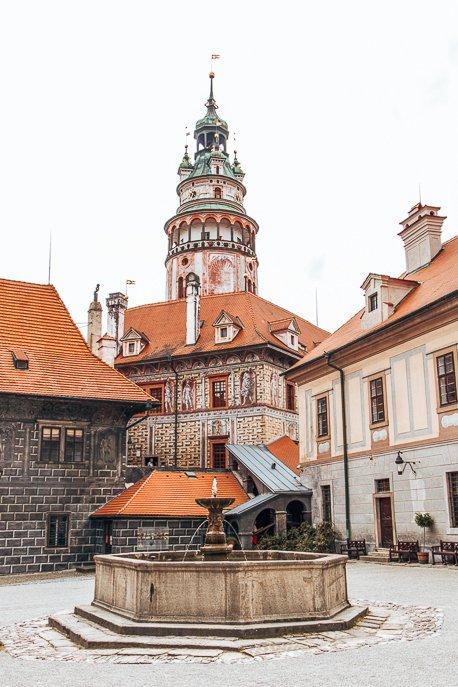 A fountain and view of Cesky Krumlov Tower from an inner courtyard, Cesky Krumlov