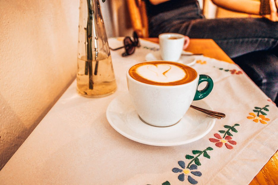 A flat white coffee on a floral embroided tablecloth at Ideal Coffee, Český Krumlov