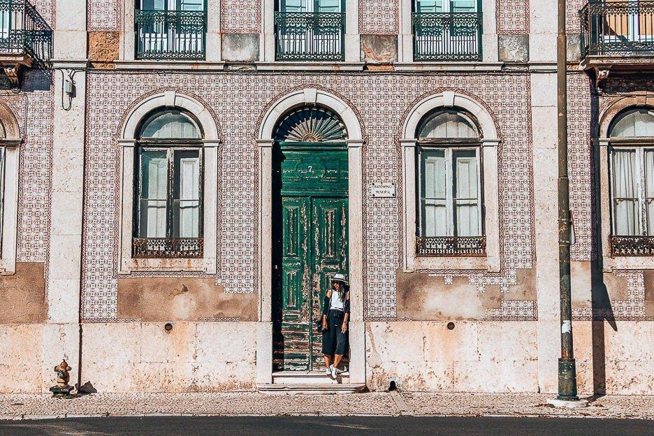 Jasmine posing in a green doorway next to pink Portuguese tiles, Lisbon