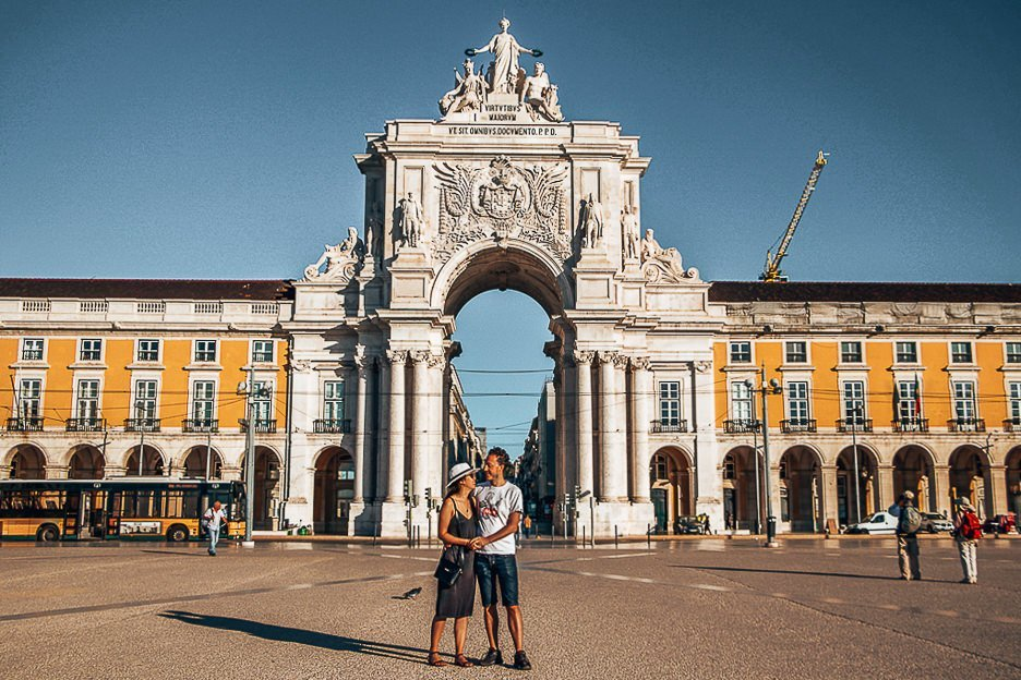 A couple post for a photo in front of Rua de Augusta in Lisbon Portugal