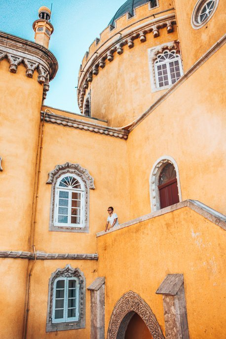 Bevan stands on a balcony amidst the yellow castle walls of Pena Palace, Sintra - Lisbon