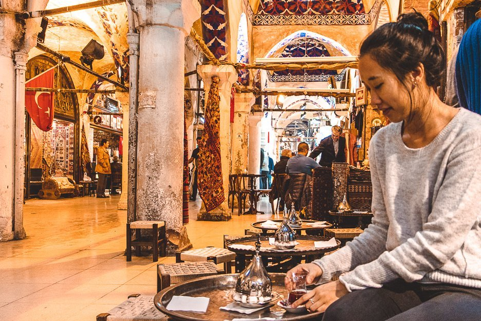 A girl sits on a low stool sipping cay in the Grand Bazaar, Istanbul