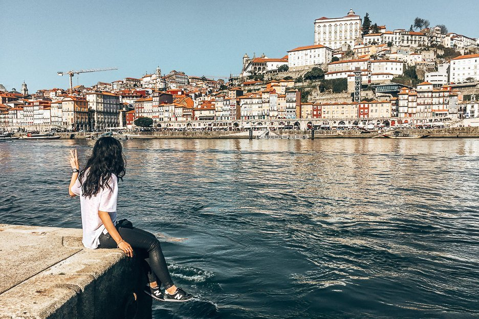 Jasmine sits at the harbourfront across for Porto city, Portugal