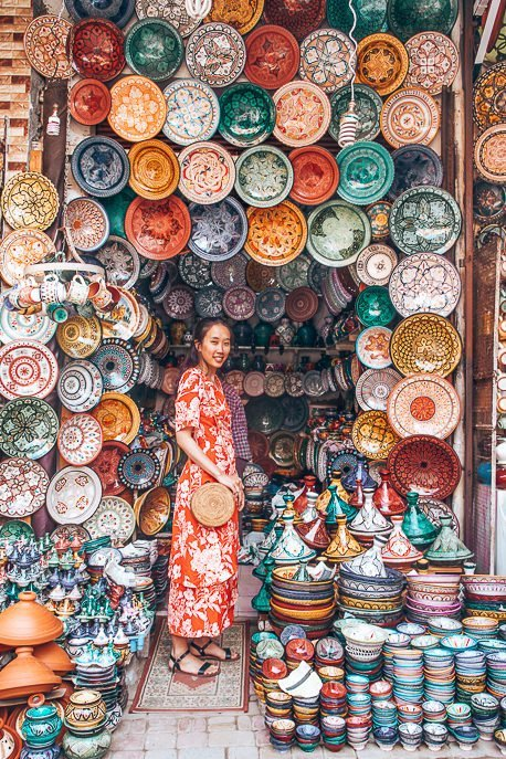A woman in a red dress stands at the entrance of a ceramics shop in the souks of Marrakech, Morocco