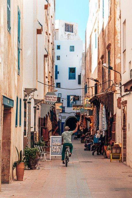 A man rides a bicycle down a narrow lane in Essaouira medina, Morocco