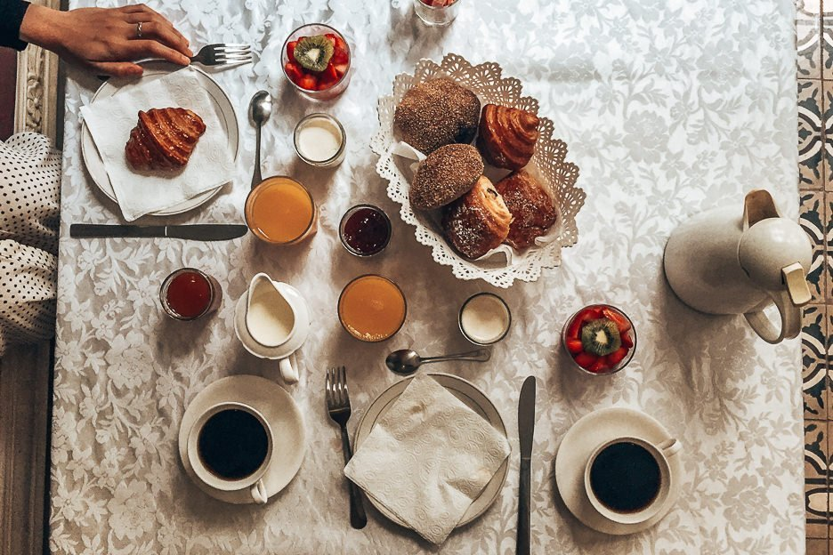 Breakfast spread of fresh pastries, yoghurt and fruits, orange juice and coffee at Riad Alnadine, Marrakech, Morocco