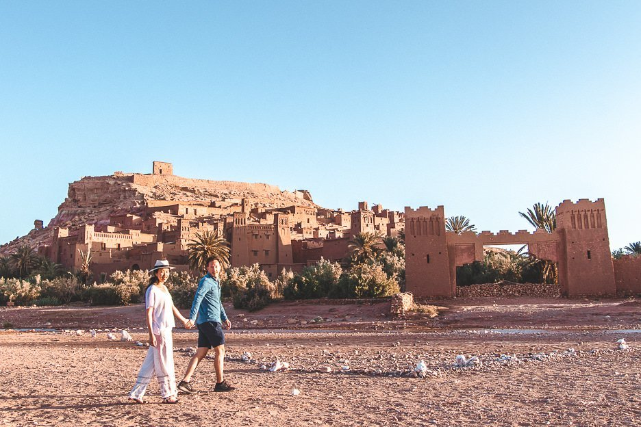 A couple walk hand in hand in front of the ancient kasbah of Ait Benhaddou, Morocco