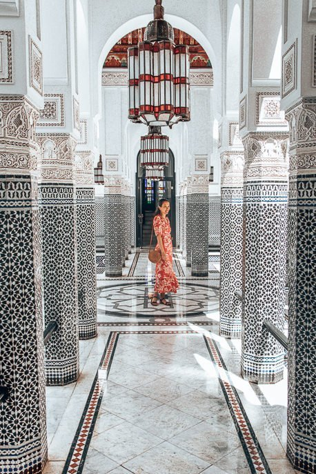 A woman in a red dress twirls in a black and white mosaic atrium in La Mamounia, Marrakech, Morocco