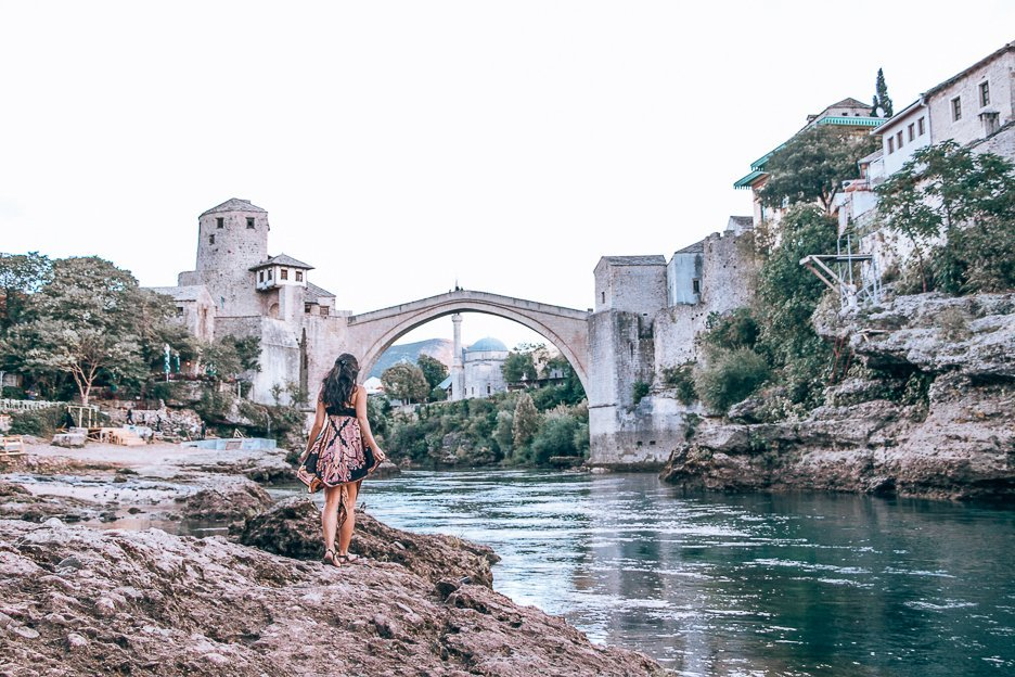 Jasmine walking by the banks of the Neretza River in front of the Stari Most in Mostar, Bosnia & Herzegovina