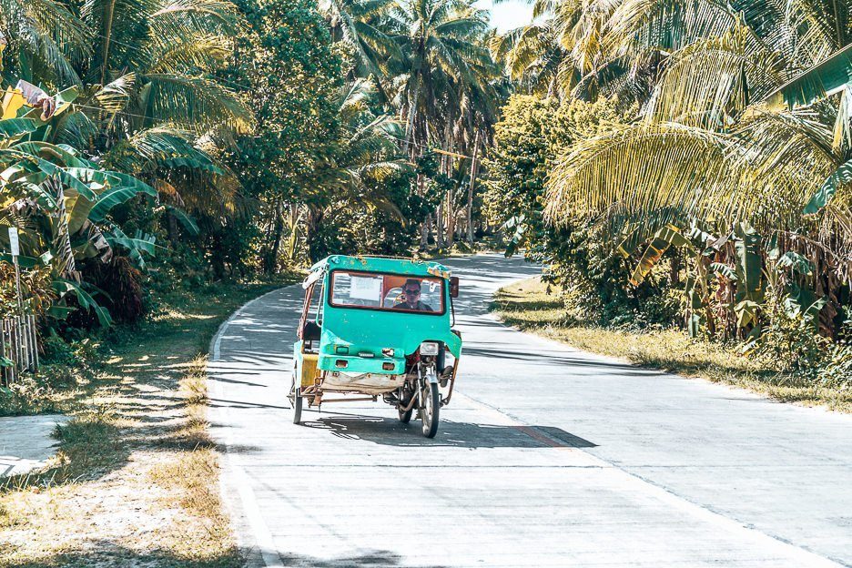A green tricycle trundles along Tourism Road, Siargao