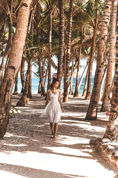 A girl in a white dress walks through the palm trees at Cloud Nine, Siargao