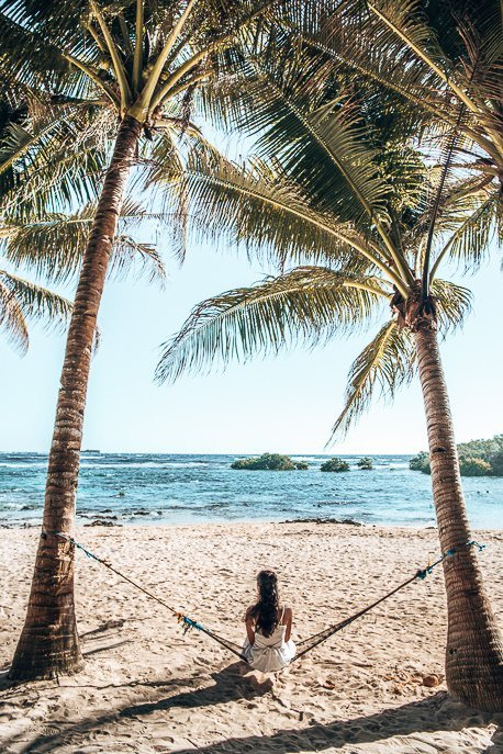 A girl sits on a hammock between two palm trees on Cloud Nine beach, SIargao