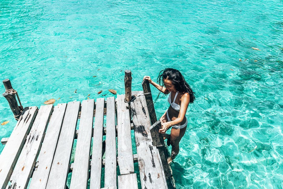 A girl steps down the ladder into the water at Sugba Lagoon, Siargao