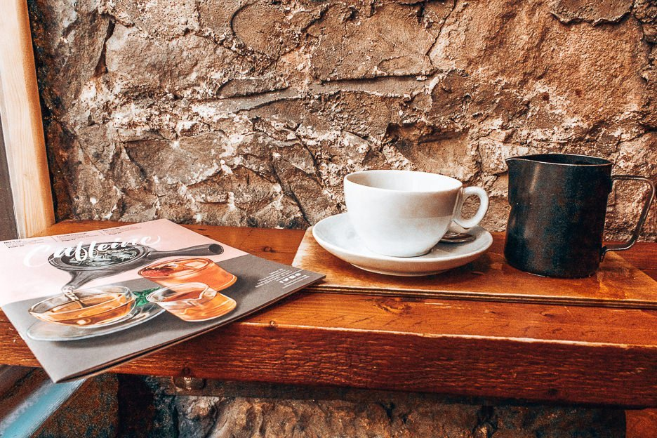 Filter coffee and magazine on a bench table at Brew Lab, Coffee in Edinburgh