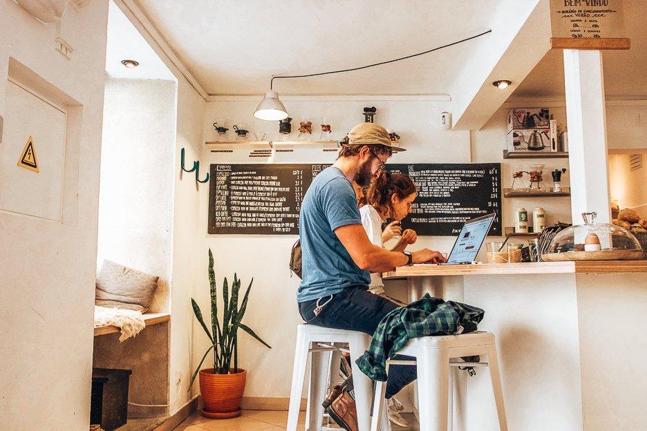 Customers on laptops in Copenhagen Coffee Lab, Lisbon Portugal