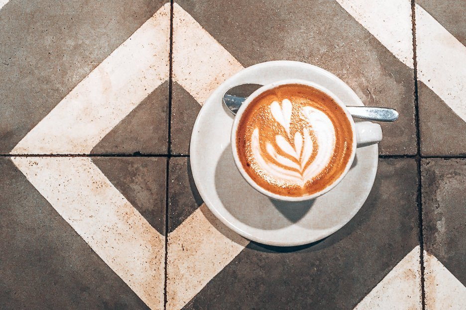 A flat white on black and white table tiles at Association Coffee, London