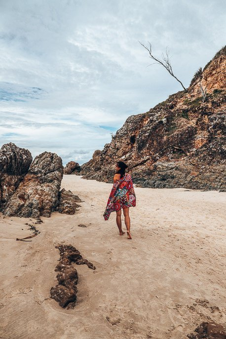 A girl walks on the sand at the Pass in Byron Bay with the Bohemian Tesalate towel around her shoulders